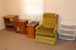 Plastic drawers, green upholstered chair, wooden clothes hamper, end table/magazine holder, and microwave/storage cart
