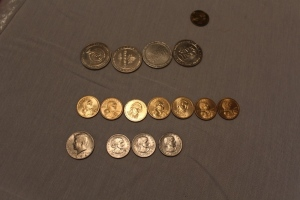 4 one dollar gaming token, 7 one dollar coins, 3 Susan B. Anthony coins, 1 half dollar 1974