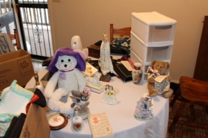 Assortment of purses, plastic storage drawers, coasters, Fatima statue, figurines, musical bear, and misc.