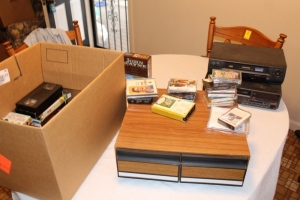 VHS tape assortment, cassettes, 2 VHS players, John Wayne DVD collection, and misc.